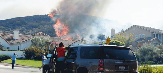 Residents look on as a back fire set by firefighters consumes the hillside behind their homes as a wildfire burns on May 2, 2013 in Newbury Park, Calif. (Photo by Kevork Djansezian/Getty Images)